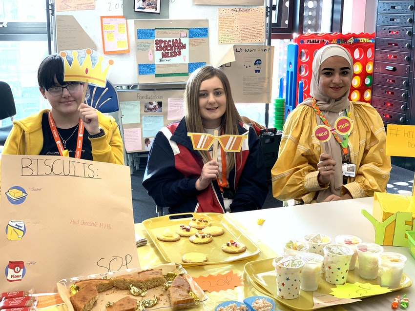 Students Abigail Emily and Heba at the stall with cakes and donation box