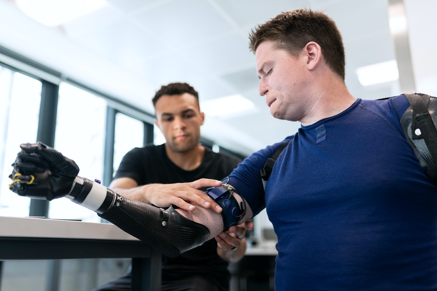 Mechanical engineer fitting a prosthetic limb