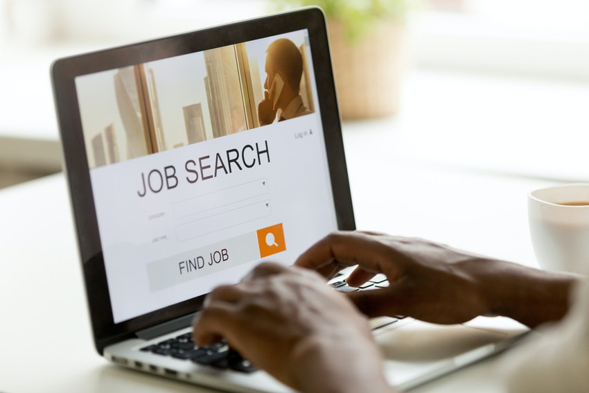 A Person Searching Online For Jobs On A Laptop