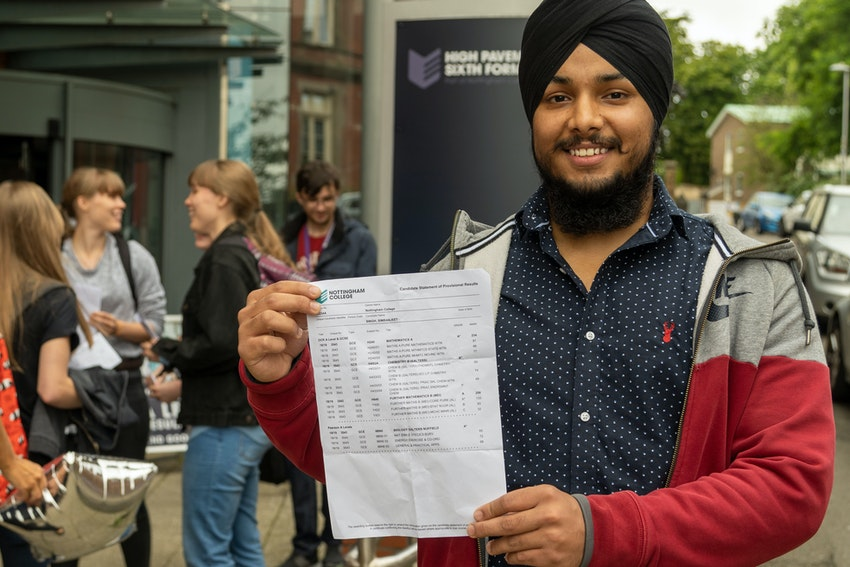 Simranjeet standing outside High Pavement Sixth Form holding his A Level results