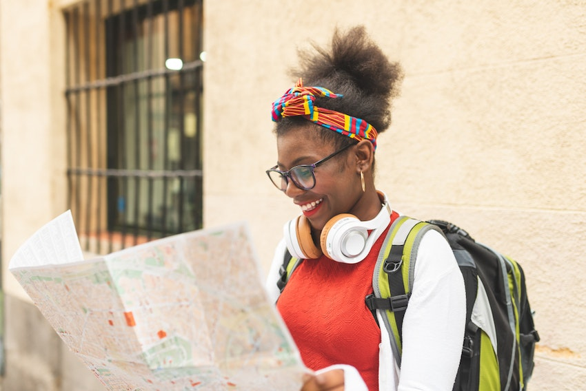 Young Person With A Backpack Reading A Map