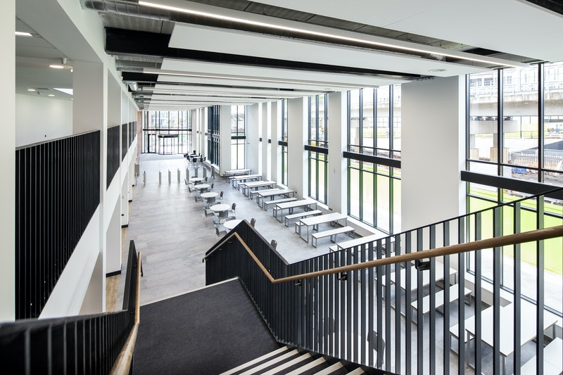 Interior of the entrance taken from a staircase from opposite end of the building, showing canteen and entrance doors