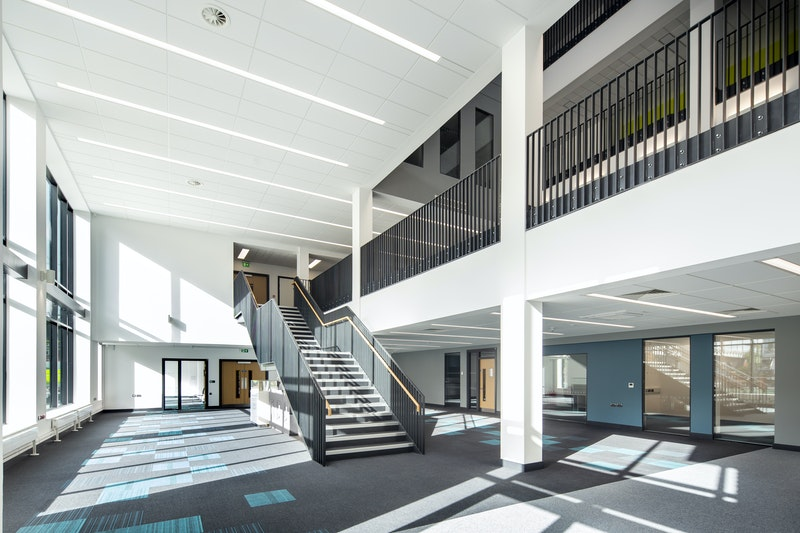 Interior of an open space with various rooms and a staircase leading to another floor