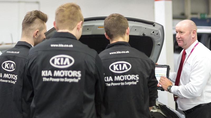 Three Kia apprentices with their back to the camera listening to an assessor talking in a workshop with several cars in the background
