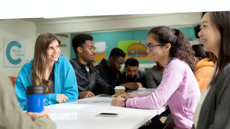 Students sitting in a canteen at a table talking to each other