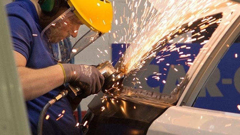 A student using a grinder creating sparks on a vehicle
