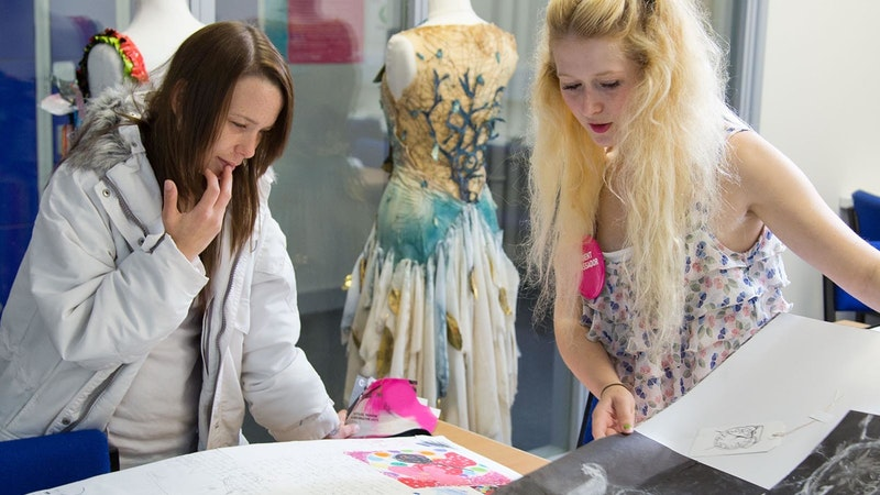 A visitor looking at art portfolios with a student ambassador