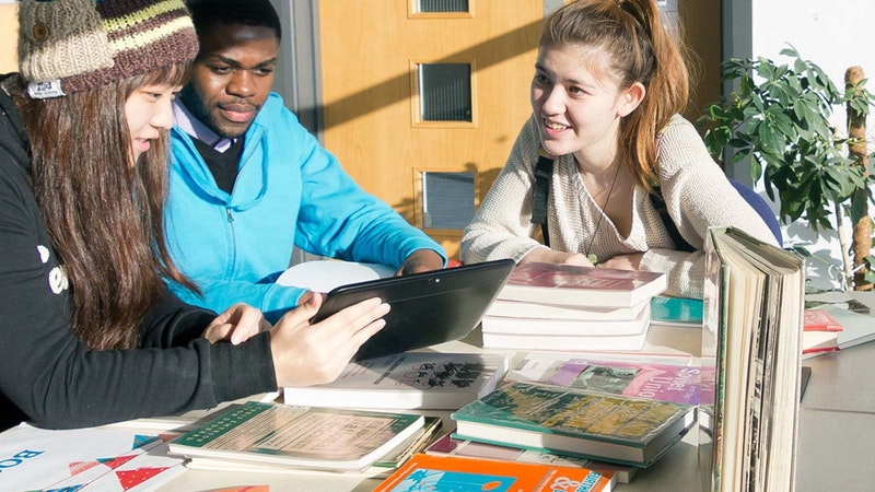 A group of students smiling at Beeston sitting at a table with books on the table surface