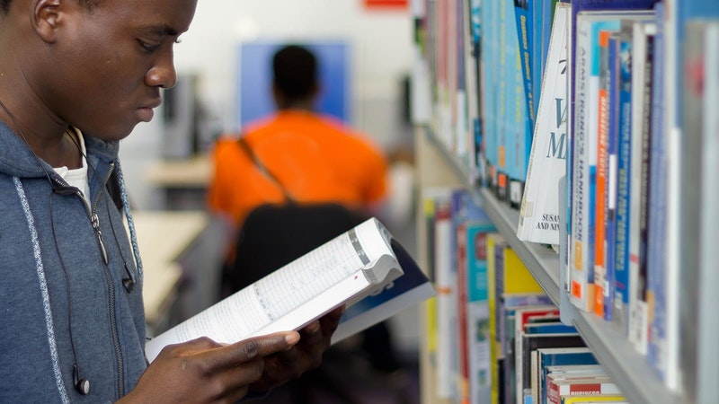 A male student reading a book taken off a library self