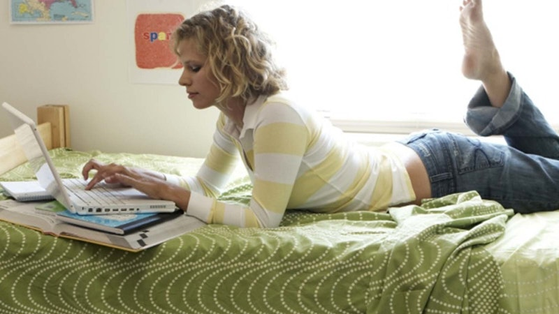 A lady using a laptop, laying on her front with book scattered across a bed
