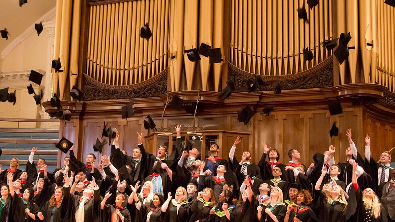 Higher Education graduates throwing their mortar boards up into the air inside the Royal Albert Hall, Nottingham