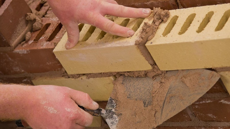 Hands of bricklayer holding a trowel laying bricks