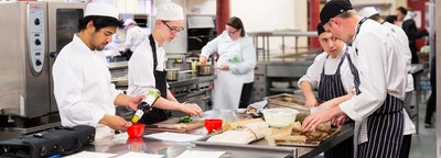 A group of catering students working in a kitchen, preparing food