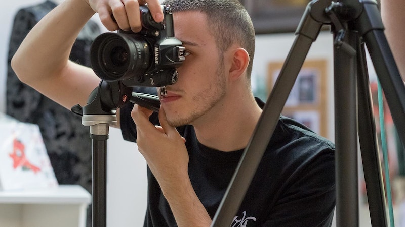 A male photography student holding a camera and taking a picture on a photoshoot