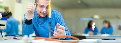 A science student using a Bunsen burner with a high flame in a science lab