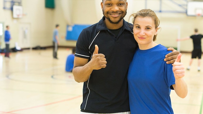 A sport teacher with a sports student standing together with their thumbs up with other students doing sport in the background