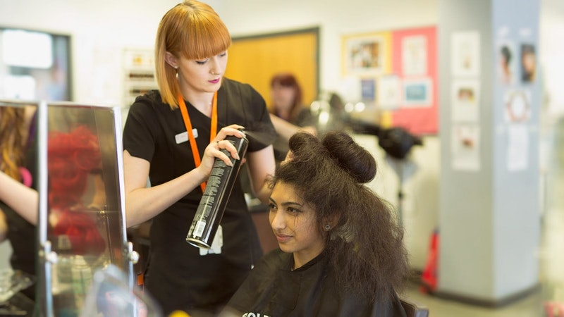 A female hairdressing student putting hair spray on a client's hair in a salon