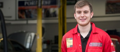 A motor vehicle apprentice standing outside the garage at London Road in red overalls