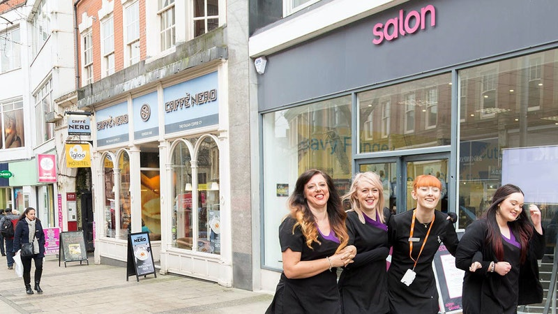 Hair and Beauty students walking past Wheeler Gate salon with their arms linked