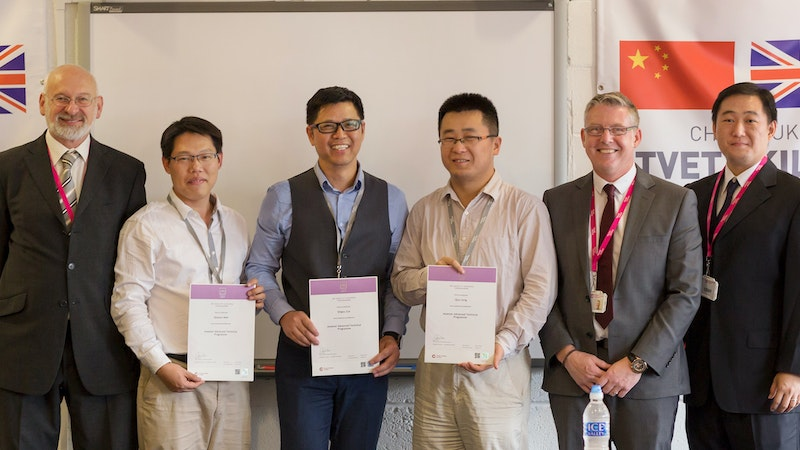 A group of Chinese delegates holding their IMI certificates with Emtec Colleges staff