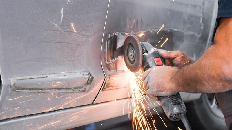 A vehicle repair apprentice cutting out damage on car bodywork with a grinder