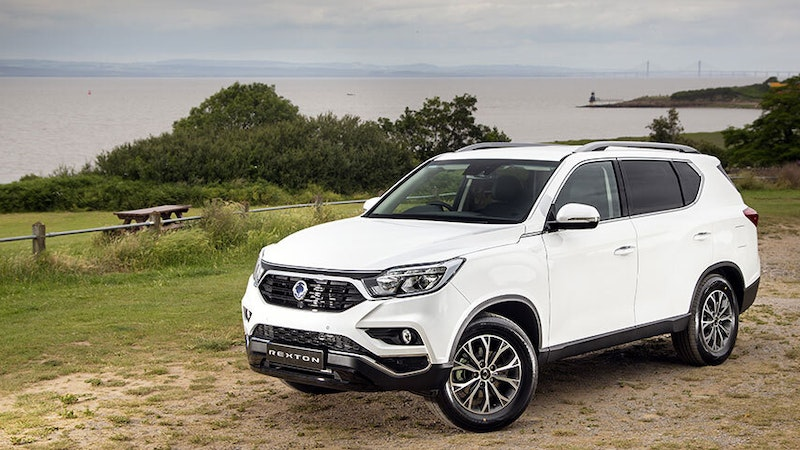 SsangYong Rexton ICE sports utility Cecile with grass, trees and sea in the background