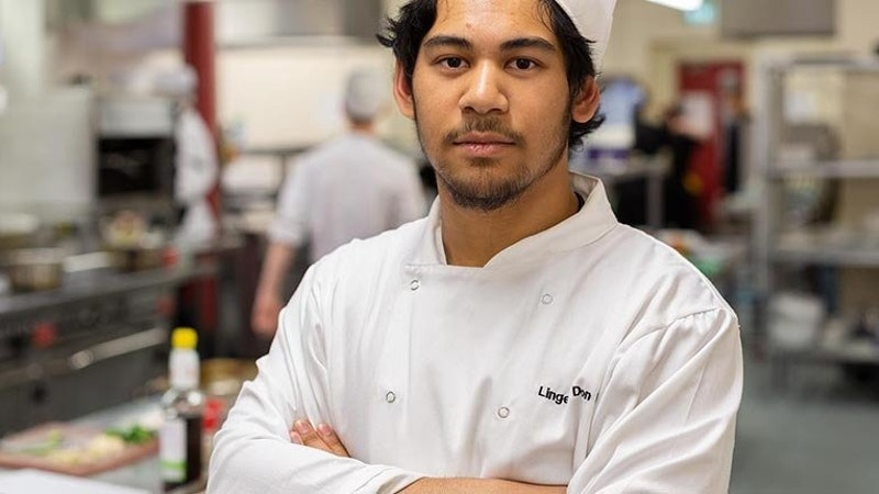 A student chef with their arms folded posing in front of a kitchen preparation area