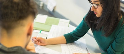 A student finance staff member helping a student fill out an application form at a table