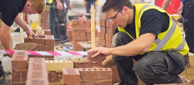 A construction student crouching down by some bricks, placing one on cement
