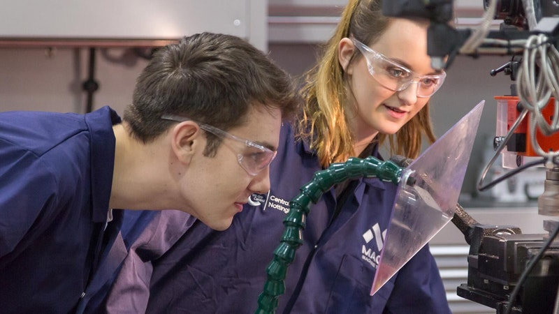A male and female engineering student examining a machine in a workshop