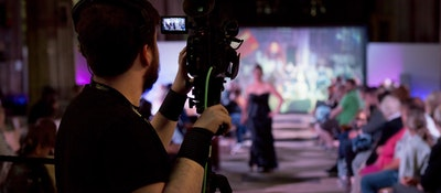 A media student standing behind a camera filming a fashion show stage