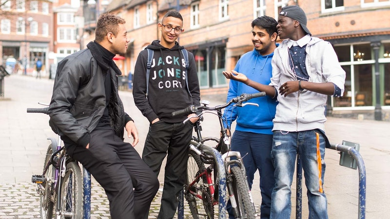 A group of students standing around a bike lockup talking in Nottingham city centre