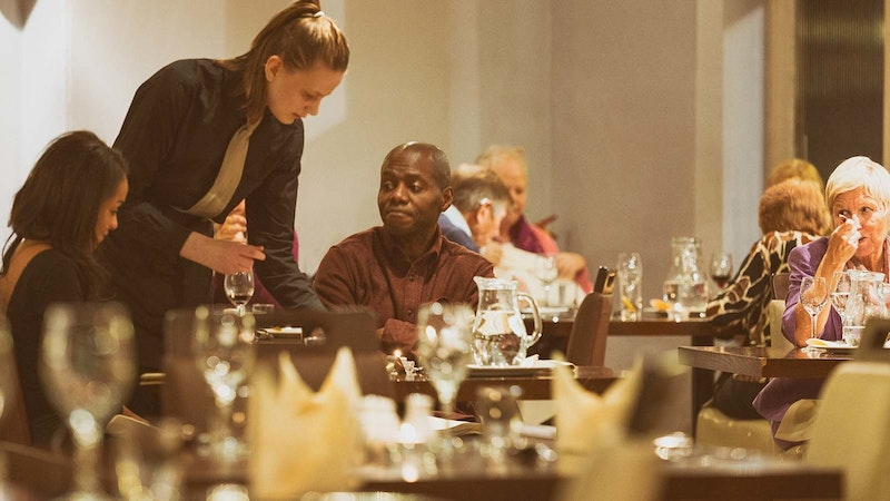 A catering student serving two customers sitting at a table in Adams Restaurant, surrounded by other dining guests