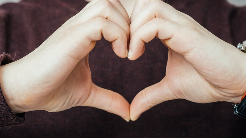 A person making a heart symbol with their hands